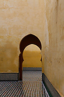 Mausoleum of Moulay Ismail, Meknes, Morocco, 1703, built by Ahmed Eddahbi, pictured on December 21, 2009. An archway in typical Islamic design, enhanced by deep shadow, pierces a stuccoed wall. Through it stretches a tiled ceramic floor in geometric pattern, contrasting with the soft apricot walls. Meknes, one of Morocco's Imperial cities, was redeveloped under Sultan Ismail Moulay (1634-1727). It is a fortified city built from pise, or clay and straw, and was designed to be the political capital of Morocco, as opposed to Fez, the religious capital. Picture by Manuel Cohen