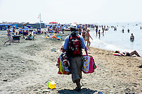Roma 16 Luglio 2013<br /> Un venditore ambulante vende oggetti sulla spiaggia di Ostia..<br /> An illegal street seller moves down the Ostia beach to avoid being discovered by police