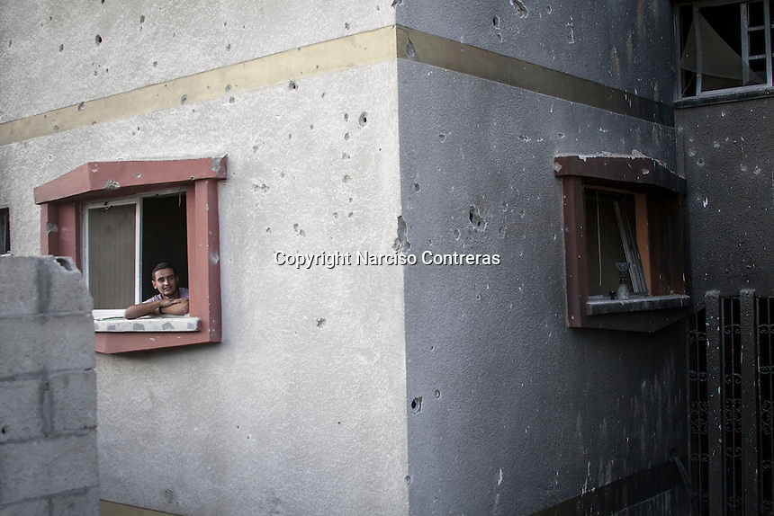 "In this Friday, Aug. 15, 2014 photo, a piece of artillery shell and one Palestinian man are seen at the windows ledges of a house building in Shuyaja neighborhood after the ""Protective Edge"" Israeli military operation reached a cease-fire in Gaza. After a five days truce was declared on 13th August between Hamas and Israel, civilian population went back to what remains from their houses and goods in Gaza Strip. (Photo/Narciso Contreras)"