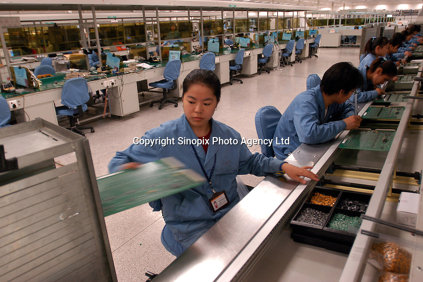 Workers assemble circuits on a production line in a factory of Datang Telecom Technology and Industry Group in Xian, China..09-NOV-02.