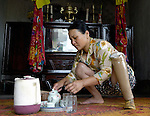 Nguyen Thi Xoan, who lost her leg to unexploded ordnance remaining from the U.S. war against Vietnam, makes tea at her home in Quang Phu.