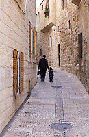 A father walks with his young child on a narrow street in the Jewish Quarter of the Old City of Jerusalem.
