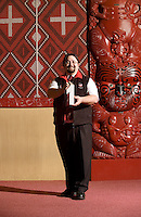 Maori man displays number one symbol, against a backdrop of meeting-house carvings at Te Aute College, Hawkes Bay, New Zealand. Photographed for a New Zealand Post editorial.