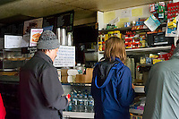 Customers wait in line at a deli, one of the few open because of the power outage, in the New York neighborhood of Chelsea after Hurricane Sandy, seen on Tuesday, October 30, 2012. Hurricane Sandy roared into New York disrupting the transit system and causing widespread power outages. Con Edison is estimating it will take four days to get electricity back to Lower Manhattan. (© Frances M. Roberts)