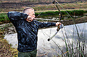 WA11806-00...WASHINGTON - Bow hunter Phil Russell hunting for bull frogs in a small pond.  (MR# R8)
