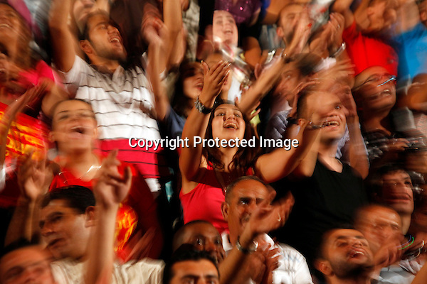 JERASH, JORDAN- JULY 28: Fans react to Lebanese singer Najwa Karam as performing at the southern amphitheatre during the Jerash Festival on July 28, 2011 in Jerash, Jordan. The Jerash Festival is a cultural event held at the end of July and beginning of August featuring a wide variety of performances. (Photo by Salah Malkawi/ Getty Images)