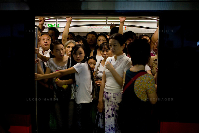 Pedestrians crowd into a subway car in Beijing, China on Tuesday, August 5, 2008. Public transportation has become increasingly crowded following the restrictions on private motor vehicles. The city of Beijing is gearing up for the opening ceremonies of the Olympic Games.  Kevin German
