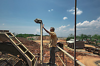 Indonesia - Bangka Island - Pemali - Stephanus Hidayat, 54, a concession owner from Belinyu supervising his concessiong and hailing at his workers. Together with other 4 businessmen, he has the biggest PT Timah mining concession in Bangka. The concession is 200 hectares, and produces 3 tons of tin ore per day. It employs 150 people in tin mining and washing lines.