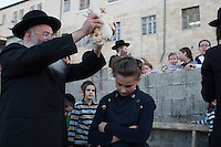 Ultra Orthodox Jews perform the Kaparot ceremony on September 10, 2013 in Jerusalem, Israel. The Jewish ritual is supposed to transfer the sins of the past year to the chicken, and is performed before the Day of Atonement, or Yom Kippur, the most important day in the Jewish calendar, which this year will start on sunset on September 13.  Photo by Oren Nahshon