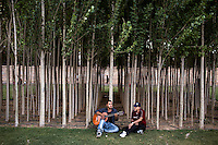 A young man plays a guitar in a park in Shiraz.