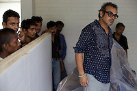 Subodh Gupta, contemporary artist in his studio in Gurgaon with freight staff about to collect a sculpture for delivery to a European exhibition.  ..Gupta's most celebrated sculptures are constructed from common domestic items including the steel pots and pans that are a feature every Indian home. Of the kitchen-ware that forms the basis of his work, Gupta says,..&quot;The poor, the middle class and the rich use it at home. In this country, how many people have the utensils but they starve because there is no food?&quot;..Gupta was brought up, one of six children, to a railway-worker father in a north Indian village. ..Gupta's work fetches such huge sums of money. Two versions of his Mind Shut Down, modeled on the human skull and constructed entirely of steel kitchen utensils recently sold for EUR1 million each...Photo: Tom Pietrasik.Gurgaon, Haryana. India. .July 23rd 2009