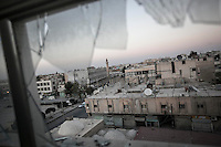 A view of Manbij city at the sunset thorugh a window from a building crashed by aircraft shelling.