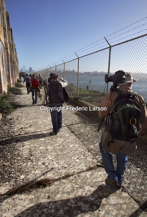 A group of photographers from the Media Alliance march single file through mounds of bird droppings towards the hospital on Alcatraz Island on San Francisco Bay. .