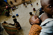 From Women work in West Africa serie..A young girl take care of a child while her mother is fishing. Guinea Conakry