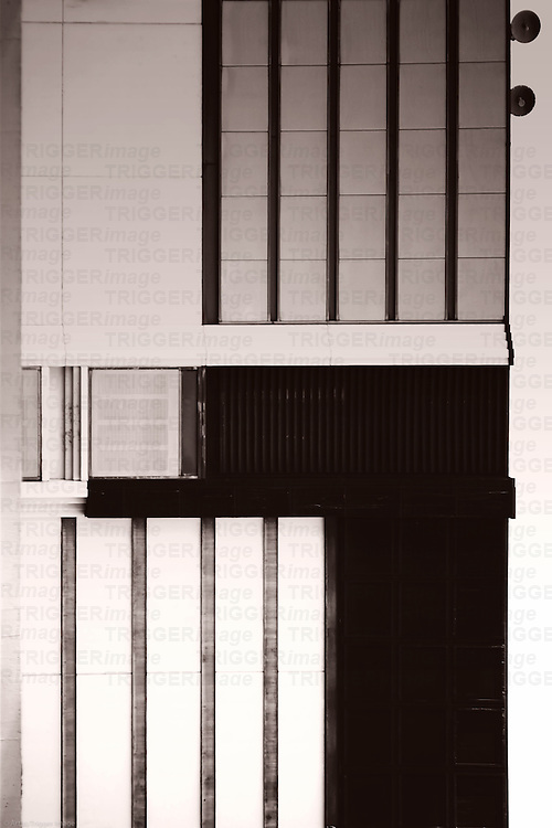 The nested facade of a business building with clouds reflections in windows and ventilation grilles.