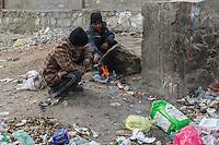 Two Kabul street children keep warm by burning plastic near a rubbish tip. 7-1-14