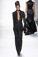 Model walks runway an EBONY SILK OTTOMAN LE SMOKING BAZER ATTACHED SILK SATIN SCULPTED COLLAR, AND EBONY SILK OTTOMAN LEAN TROUSERS W/ SILK SATIN WAISTBAND by Zang Toi, for the Zang Toi Spring 2012 My Dream Of North Africa Collection, during Mercedes-Benz Fashion Week Spring 2012.