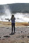 A young girl walks towards bison warming themselves next to hot pools in Yellowstone National Park.