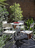 On the first floor balcony a garden table and chairs of painted metal are surrounded by trees and shrubs in terracotta pots