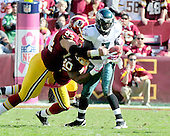 Philadelphia Eagles quarterback Michael Vick (7) is sacked by Washington Redskins safety Oshiomogho Atogwe (20) and defensive lineman Kedric Golston (64) late in the third quarter at FedEx Field in Landover, Maryland on Sunday, October 16, 2011.  The Eagles won the game 20 - 13..Credit: Ron Sachs / CNP