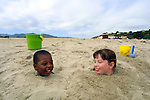 Sam and Bayley Baskow enjoy the fun of being buried in the sand on the California Coast.