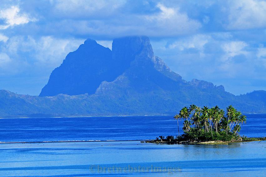 A small motu (atoll island) adorns the brooding peak of Bora Bora.