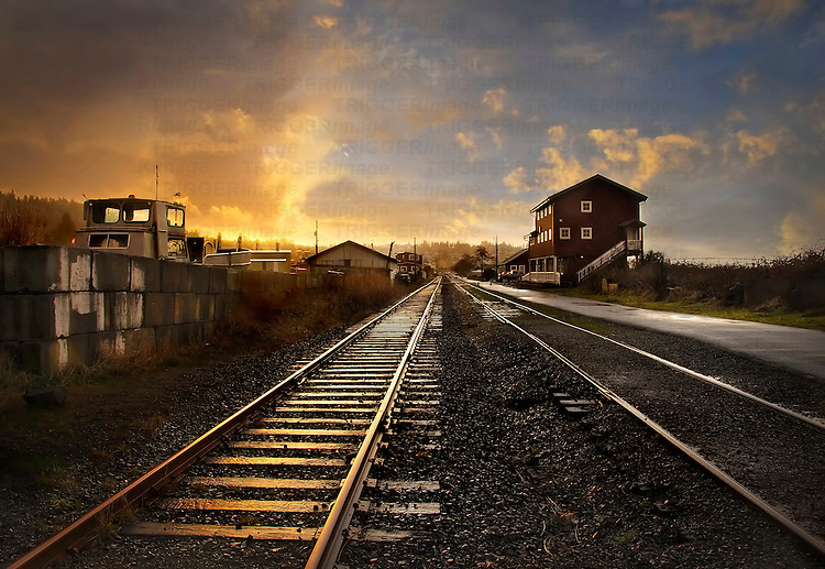 A railway track leading into the distance through a small station at sunset