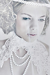 Close up of a young female face with blonde hair wearing white lace and pearl necklace
