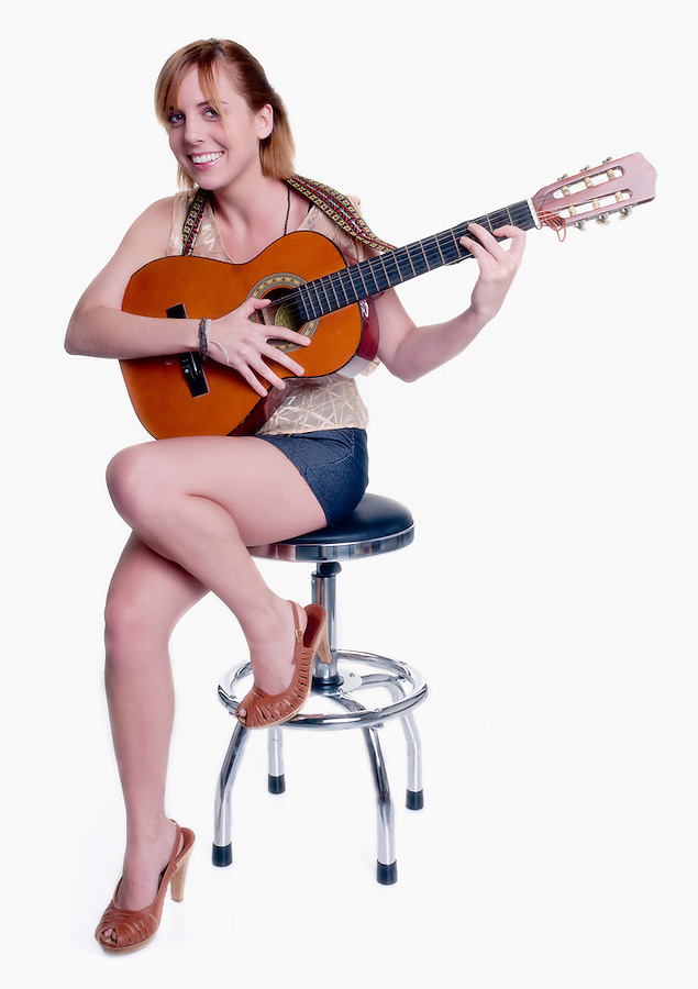 Young woman playing guitar and smiling looking at camera. High Key Image.