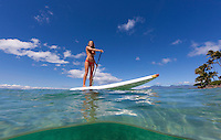 A woman enjoys a beautiful day standup paddling at Napili Bay, Maui.