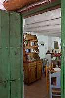 View through a green door into the living/dining room with a hand-painted dresser