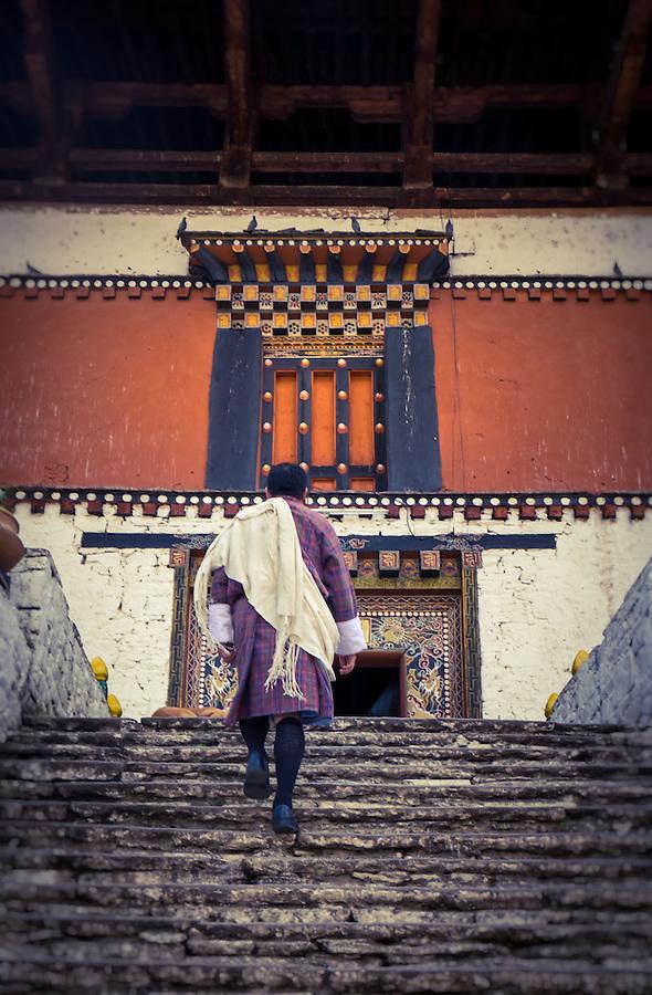 PARO, BHUTAN - CIRCA October 2014: Bhutamese man walking into the Paro Rinpung Dzong in Bhutan