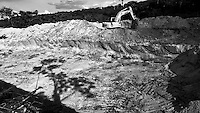 """Starting of hydraulic gold mining operation process known as """"chupadeira system"""". Use of heavy machinery for excavation, workers clear the designated work front and then dug down to the level of ore-bearing material. Large and deep holes are made in forest land where gold miners will use high-pressure jets of water to dislodge rock material and move sediments. Amazon rain forest deforestation at Agua Branca gold mining village, Para State, Brazil."""