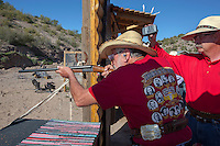 "USA. Arizona state. Peoria. Peoria is distant 50 km from Phoenix. Cowtown Shooting Range. Cowtown Cowboy Shooters Association. Fake town scenery from the old Far West time. Frank Spence is shooting targets with his Winchester rifle. He wears a silver belt with the words (SASS Arizona. Senior Duelist 2015.) and a red t-shirt with the Legends of the West ( Will Bill Hickok, John Wesley Hardin, Sitting Bull, Jesse James, George Custer, Butch Cassidy).  A group of elderly men and women, all dressed with cowboys outfits, train outdoors for the incoming Winter Range - SASS National Championship of Cowboy Action Shooting ( february 22nd-28th, 2016). The Single Action Shooting Society (SASS) is a Cowboy Action Shooting (CAS, also known as Western Action Shooting, Single Action Shooting, or Cowboy 3-Gun). CAS is a type of multi-gun match utilizing a combination of pistol(s), rifle ( Winchester), and/or shotgun in a variety of ""old west themed"" courses of fire for time and accuracy. Participants must dress in appropriate theme or era ""costume"" as well as use gear and accessories as mandated by the respective sanctioning group rules. A CAS shooter (L) engages a target with his lever-action rifle. Just behind, the range officer with a timer that measures the shooter's stage time. Cowtown Shooting Range is a semi-private outdoor shooting range and firearms training facility. A firearm is a portable gun, being a barreled weapon that launches one or more projectiles often driven by the action of an explosive force. Most modern firearms have rifled barrels to impart spin to the projectile for improved flight stability. The word firearms usually is used in a sense restricted to small arms (weapons that can be carried by a single person). The right to keep and bear arms is a fundamental right protected in the United States by the Second Amendment of the Bill of Rights in the Constitution of the United States of America and in the state constitutions of Arizona and 43 other states. 31"