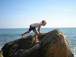 Girl climbing on a rock in the sea.  Mohegan Bluffs, Block Island.