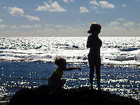 Two young girls silhouetted against the bright daylight while playing on the rocks at a beach in Kailua-Kona, Big Island.