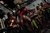 A young Cuban man, wearing a red blindfold, passes a secret initiation ritual amongst the Palo religion followers in Santiago de Cuba, Cuba, August 1, 2009. The Palo religion (Las Reglas de Congo) belongs to the group of syncretic religions which developed in Cuba amongst the black slaves, originally brought from Congo during the colonial period. Palo, having its roots in spiritual concepts of the indigenous people in Africa, worships the spirits and natural powers but can often give them faces and names known from the Christian dogma. Although there have been strong religious restrictions during the decades of the Cuban Revolution, the majority of Cubans still consult their problems with practitioners of some Afro Cuban religion.
