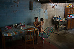 November 08, 2014. &quot;Water it&acute;s the real thing&quot;<br /> Siomara Raquel Castro with her child Bradley Jared in her home in Nejapa (El Salvador). She doesn' t have water at home. The people of Nejapa have no drinking water because the Coca -Cola company overexploited the aquifer in the area, the most important source of water in this Central American country. This means that the population has to walk for hours to get water from wells and rivers. The problem is that these rivers and wells are contaminated by discharges that makes Coca- Cola and other factories that are installed in the area. The problem can increase: Coca Cola company has expansion plans, something that communities and NGOs want to stop. To make a liter of Coca Cola are needed 2,4 liters of water. &copy;Calamar2/ Pedro ARMESTRE