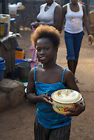 Kroo Bay, Freetown, Sierra Leone...Story on child and maternal health in the Kroo Bay slum community in Freetown, Sierra Leone, which has the World's worst infant and maternal mortalitly rates. One in 4 children die before they reach the age of 5 and one in 6 mothers dies during child birth (in the UK, the rate is one in 3,800)...The Kroo Bay Community Health Centre has a catchment area of over 8,000 people but lacks adequate facilites to provide even basic care. The clinic lacks even the basics, such as bedpans, surgical spirits and cotton wool. It has no electricity and clean drinking water must be fetched from the nearby well everyday...Isha Kamara buying cooked rice to eat for her family...© 2007 Aubrey Wade. All rights reserved.