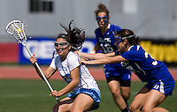 Kaitlyn Messinger (25) of North Carolina is checked by Jillian Heinz (30) of Duke during the ACC women's lacrosse tournament semifinals in College Park, MD.  North Carolina defeated Duke, 14-4.