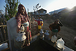 A woman fills a container with water at a community spigot in Makaising, a village in the Gorkha District of Nepal that was hard hit by a devastating 2015 earthquake.