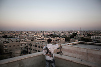 An FSA fighter appoints with the finger to the city as he stands guard at the top roof of a building in Manbij, a city located at the northeast of Aleppo province.