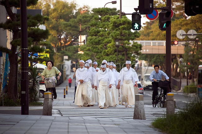 Priests carry seaweed through the town as they return from the hamaorisai ritual at Yuigahama beach during the annual Reitaisai Grand Festival at Tsurugaoka Hachimangu Shrine in Kamakura, Japan on  14 Sept. 2012.  Sept 14 marks the first day of the 3-day Reitaisai festival, which starts early in the morning when shrine priests and officials perform a purification ritual in the ocean during a rite known as hamaorisai and limaxes with a display of yabusame horseback archery. Photographer: Robert Gilhooly