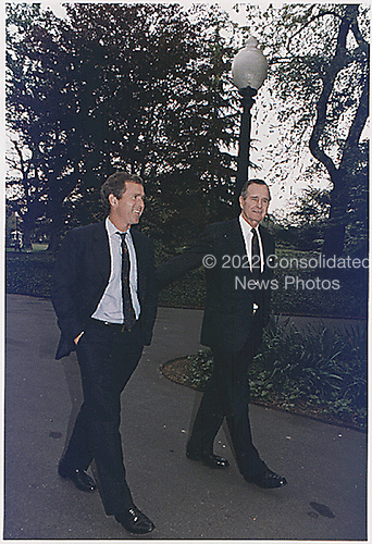 Washington, D.C. - April 29, 1992 -- United States President George H.W. Bush walks up the South Lawn towards the Oval Office at the White House in Washington, DC with his son, future United States President George W. Bush on April 29, 1992. .Credit: White House via CNP