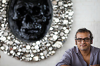 Subodh Gupta, contemporary artist with one of his sculptures in his recently completed studio in Gurgaon, a satellite town of Delhi...Gupta's most celebrated sculptures are constructed from common domestic items including the steel pots and pans that are a feature every Indian home. Of the kitchen-ware that forms the basis of his work, Gupta says,..&quot;The poor, the middle class and the rich use it at home. In this country, how many people have the utensils but they starve because there is no food?&quot;..Gupta was brought up, one of six children, to a railway-worker father in a north Indian village. ..Gupta's work fetches such huge sums of money. Two versions of his Mind Shut Down, modeled on the human skull and constructed entirely of steel kitchen utensils recently sold for EUR1 million each...Photo: Tom Pietrasik.Gurgaon, Haryana. India. .June 26th 2009