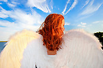 Young woman wearing spread angel wings, closeup seen from behind at dusk, at Levy Park and Preserve, Merrick, Long Island, New York, USA