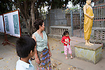 Bunroeun and family visit the local Buddhist pagoda..A Khmer boy learns to play classical violin at the college of Beaux Arts, at the edge of Cambodia's capital, Phnom Penh. He is an orphan and comes from a poor family. His parents died long ago, from AIDS related diseases. He lives with his grandmother and his uncle, and their family. He lives on the top floor of an apartment block, where his family run a textile business, sewing together clothes and ornamental flags from around the world. A dozen young women work in this textile business, and the boy's home space is actually amidst this small factory environment which he shares with them. They eat, work and play together like an extended family or community. Phnom Penh, Cambodia