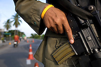 "An armed soldier wears a wristband with the inscription ""Long live the King"" at one of the many checkpoints in and around the town of Pattani. The insurgency in Southern Thailand began as a conflict between the Malay muslim population and central government, but now the boundaries have become blurred and various guerilla groups have become involved. No-one seems certain as to who is fighting who. As of March 2008, the insurgency had claimed as many as 3,000 lives."