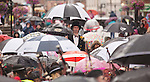 A wet Guid Nychburris in Dumfries. British summer weather rain rain and more rain. Man on stilts with umbrella standing above a sea of umbrellas in the pouring rain
