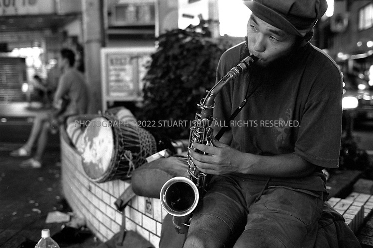 "8/10/2002--Shimokitazawa, Tokyo, Japan..A saxophonist plays for money outside Shimokitazawa train station...Wedged between Tokyo's Shinjuku and Shibuya wards, Shimokitazawa's maze of narrow streets form the ramparts of all that is non-conformist in get-along, go-along Japan. In ""Shimokita,"" old village shops trade happily beside newer, eccentric clothing stores, funky restaurants, matchbox playhouses and live-music clubs. The unpretentious ambience is a magnet for students and other young visitors for whom Tokyo's usual street fashion scene has become more fascist than fun and mainstream entertainment is, well, too mainstream. Musicians, designers, aspiring actors and other would-be iconoclasts have settled the area, as have young professionals opting for a less-structured lifestyle. ...All photographs ©2003 Stuart Isett.All rights reserved.This image may not be reproduced without expressed written permission from Stuart Isett."